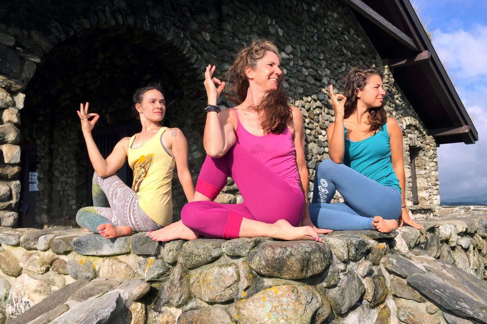 three women in matsyendrasana on a wall