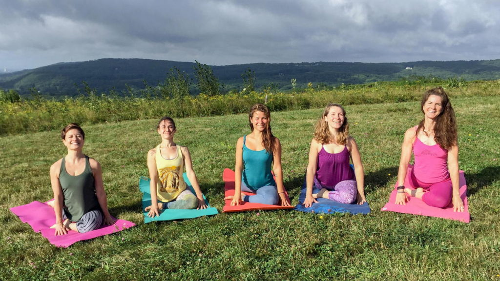 A line of women in pigeon pose on a hilltop