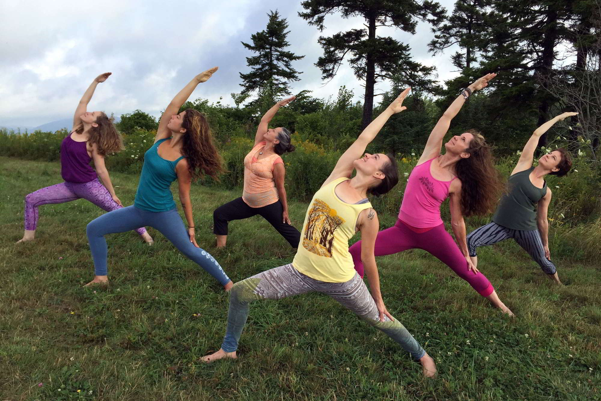 a line of women perform virabhadrasana II in a field