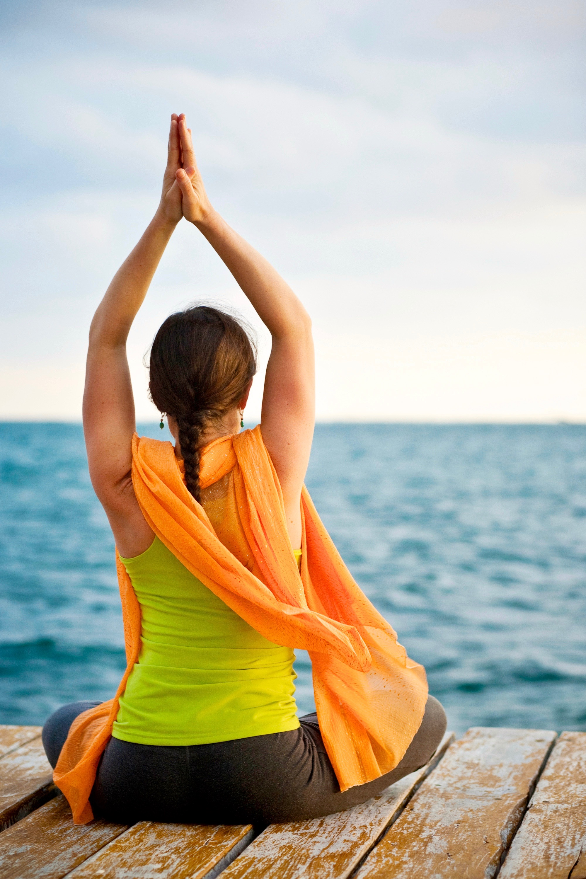 Seated yoga posture on a dock by the water