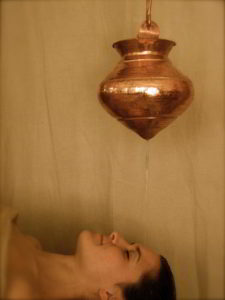 infused oils pour onto a woman's head during Shirodhara