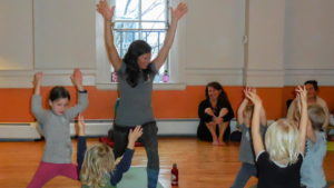 a teacher leads a children's yoga class