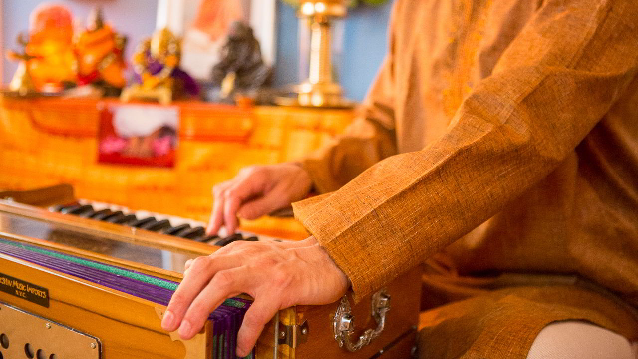 close up of a harmonium player's hand in a Bhakti yoga class