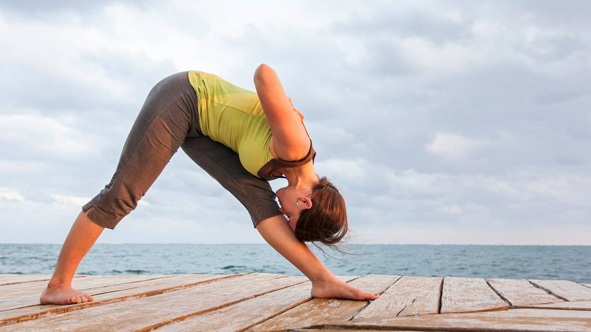 Aiyana performs a forward bend on a dock by the water