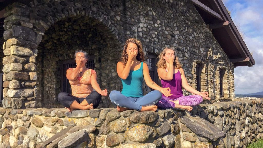 3 women practice Pranayama on a rock wall outdoors