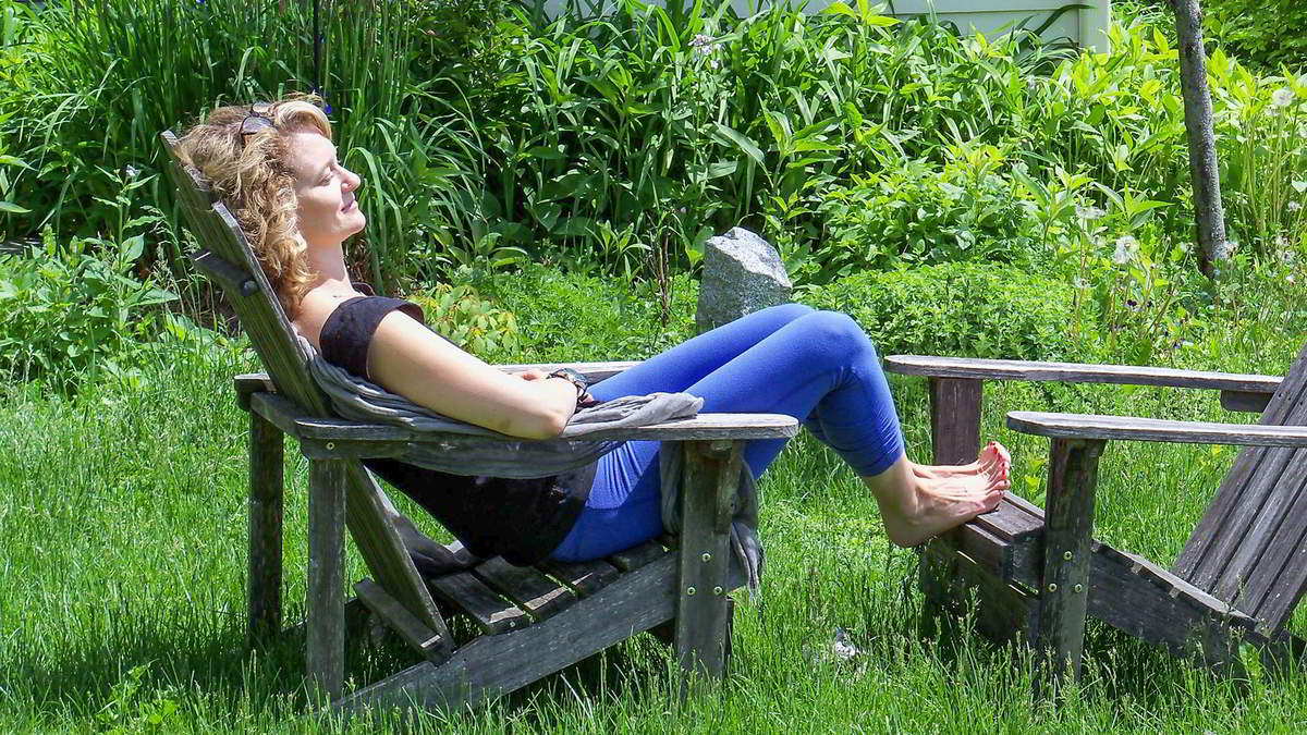 A woman relaxes in a chair outdoors during a retreat
