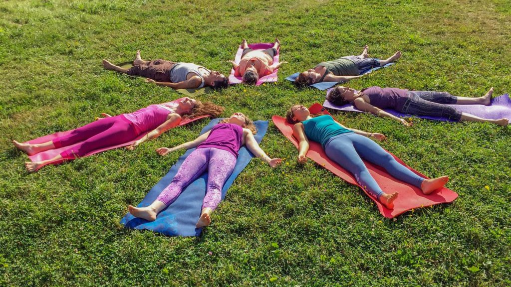 A circle of people lie in Svanasana on a hilltop