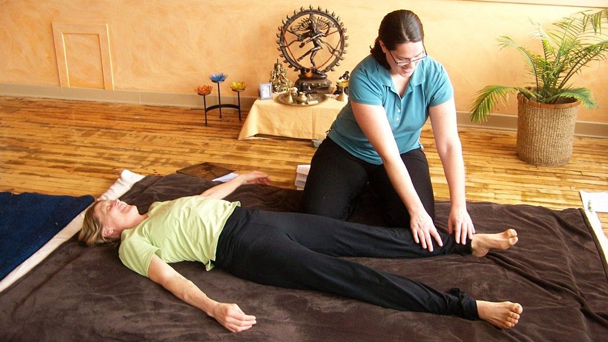 A students practices Thai massage on a partner