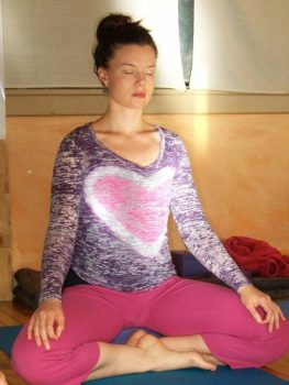 a woman sits in meditation