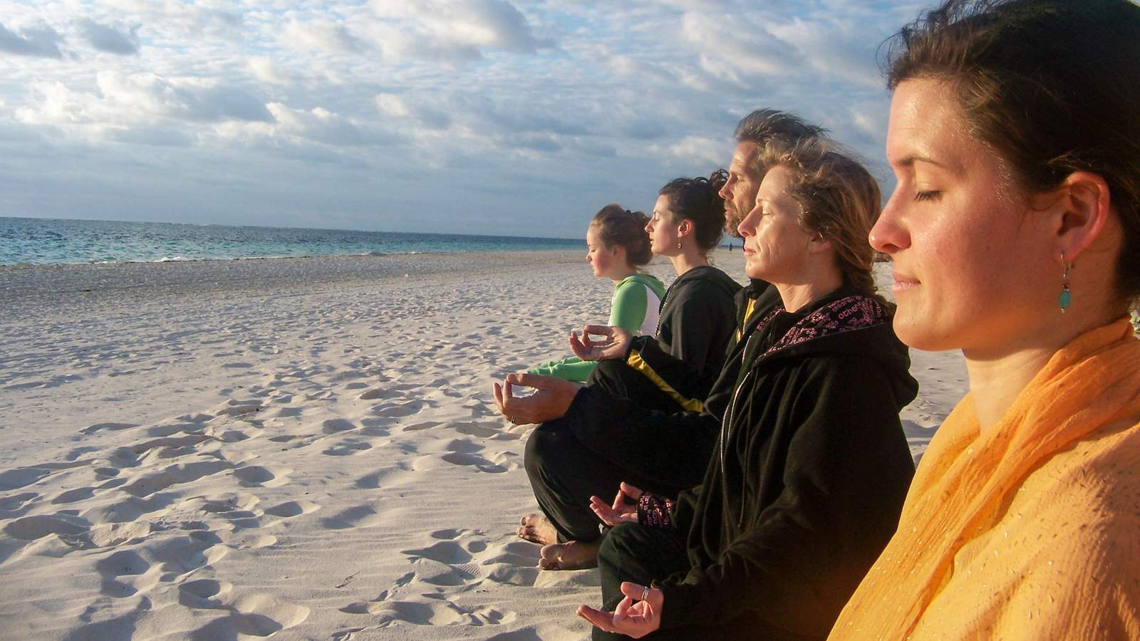 A line of practitioners meditating on a beach in Mexico