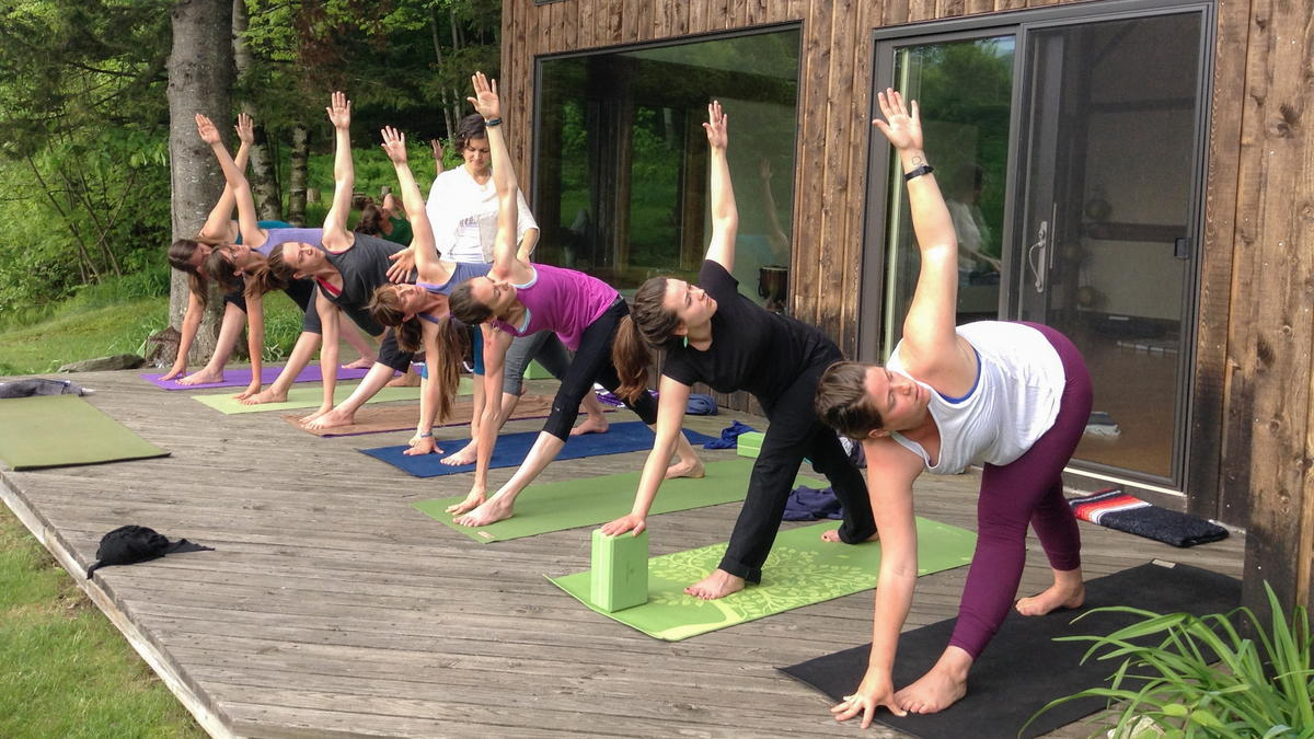 A yoga class performs a twist on a deck outdoors