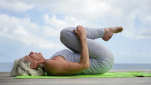 A senior woman performs restorative yoga on a dock by the ocean